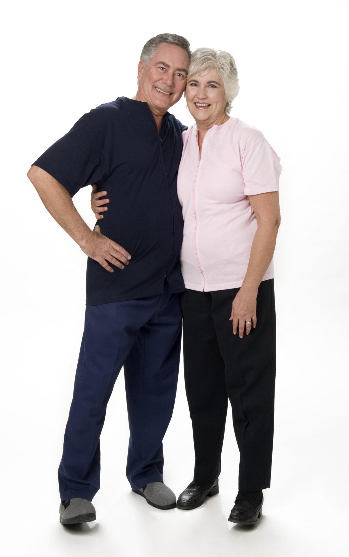 Full length studio photo of mature couple standing. White background.